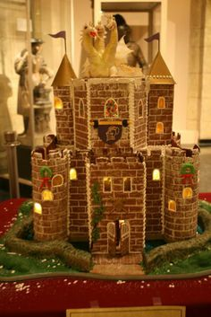 Gingerbread Castle: We love the faux brick and festive wreath details on this extravagant castle. A super detailed three-headed dragon straight out of a fantasy story tops it all off. Gingerbread Castle, Gingerbread Decorations, Christmas Gingerbread House, Christmas Treats, Christmas Time Is Here, Winter Christmas, Christmas Shop Displays, Cookie House, Castle Wall