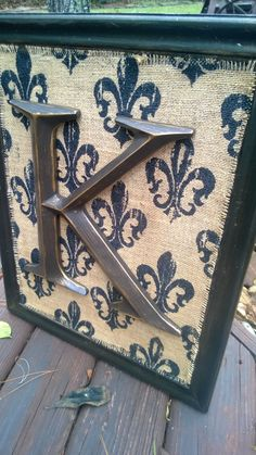 Repurposed cabinet door, black and metallic brown glaze, fleur de lis burlap and owner's initial!