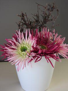 Een strak wit potje met licht roze en donker roze zijden bloemen. www.abonneefleur.nl