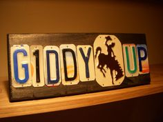 GIDDY UP sign made with recycled license plates including the Wyoming bucking bronco.. $34.00, via Etsy.