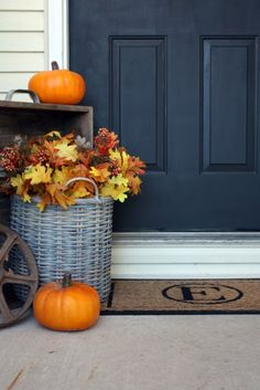 Reusable fall decoration -- plastic pumpkins and leaves in an aged wicker basket. Also DIY monogram doormat!
