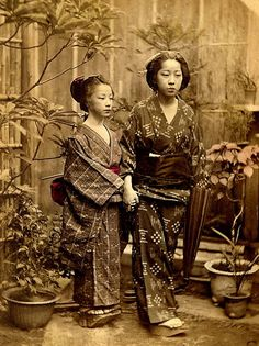 A walk in the garden. A warm portrait of two young Japanese women. Notice their shoes and how tiny they must be without them. Ca. 1870s-80s.