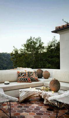 Une terrasse avec tomettes et banquettes blanches pour profiter de l'été