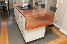 the island is from Ikea, but they swapped in Restoration Hardware pulls and added a copper top. A hinged leaf can flip up to provide more surface area.