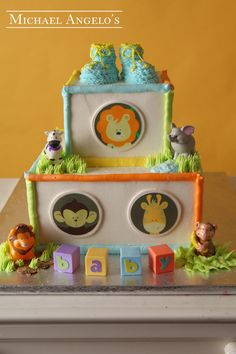 Booties with Animals #22Baby This two-tier square buttercream cake is accented with plastic zoo animals, and zoo animal edible images. Baby blocks and buttercream booties were also added to complete this baby shower cake.