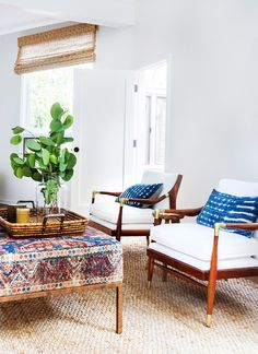A bohemian chic California home: ottoman upholstered in vintage textiles with a patinated brass frame, arranged with a pair of matching mid-century modern armchairs | Design by Amber Interiors