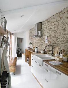 Mur de brique et de pierre dans une cuisine en longueur