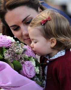 Catherine, Duchess of Cambridge holds flowers up to Princess Charlotte of Cambridge depart Victoria on October 1, 2016 in Victoria, Canada.