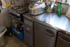 業務用冷蔵庫に4口コンロが置かれたプロ仕様のキッチン。「人が楽しんでくれること」を大切に、料理を演出。 Kitchen Island, Oven, Kitchen Appliances, Interior, Room, House, Refrigerator, Space, Home Decor