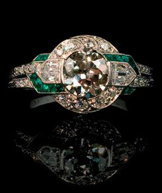 Circa 1925, an Art Deco ring by Tiffany Co., featuring emeralds and diamonds set in platinum.