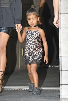 North West steps out in New York wearing a leopard slip dress, black choker and Yeezy boost sneakers. See all the toddler's best outfits here: