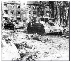 Russian self-propelled guns SU-76M pass dead German soldiers. Belarus, Spring 1944.