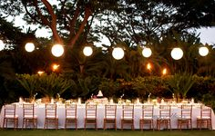 One long table with single string of lanterns overhead, specialty linen and chiavari chairs.  Garden Lawn, Four Seasons Resort Hualalai Weddings