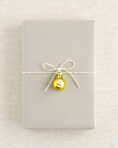 Simple gift wrap, thick grey paper, short length of white string and gold bell with white initial