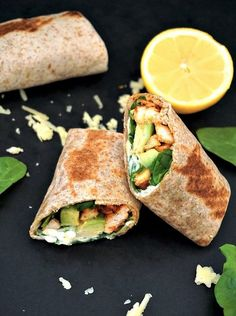 Two halves of a grilled chicken & avcado wrapped with spinach leaves, lemon slice and grated cheese around them, and another wrap in the background
