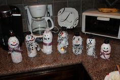 CRAFT idea for winter art party!  snowmen from plastic bottles. idea from family fun mag. covered with glue and white tissue paper. hats are black duck tape. eyes & buttons are sequins, scarf is fabric! cut bottom of snowman and place a battery-tea light. they flicker and look really cute in a group!