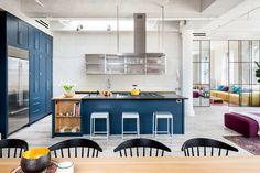 Loft w Nowym Jorku, proj. Casamanara, fot. Evan Joseph. Widok z jadalni na kuchnię. Wnętrze wygląda na uporządkowane dzięki zdyscyplinowanej kolorystyce i dyskretnie wprowadzonej symetrii.