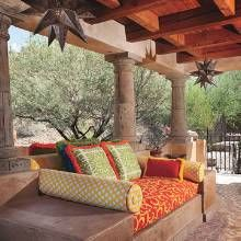 "Mexican style ""sunset terrace"" has back-to-back bancos with decked out  vibrant patterned fabrics."