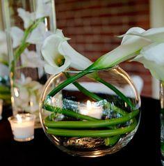 Tisch mit Kerzen und Glaskugel mit weißen Callas