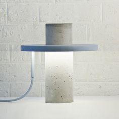 """Le designer Alexandre Dubreuil et son studio ont imaginé """"Totem Light"""", une lampe à poser composée d'un corps principal de béton et surmonté d'un plateau de bois circulaire accueillant le système d'éclairage. Le cylindre de béton brut ..."""