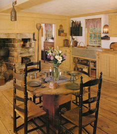 Love the old cooking fireplace, the ladder back chairs and the wide plank flooring.  However I would paint the walls and cabinets white.