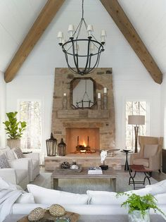 Gorgeous living room boasts a vaulted wood beam ceiling accented with and iron chandelier illuminating a white sofa and chairs facing a gray wash wood waterfall coffee table.