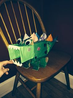 Dinosaur Valentine Box. I made with the help from my son. Used: paint, cut out upside down hearts for spikes, Popsicle sticks, google eyes, tail is old half top of 2 liter bottle. Body is Kleenex box, and mouth is the open part of a plastic storage container! All recycled material!!!:)