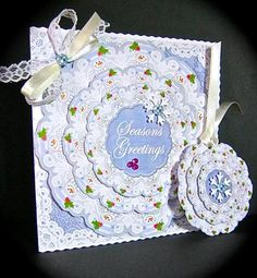 Blue Snowman Seasons Greetings 3D Doily Card Mini Kit on Craftsuprint created by Cynthia Massey - Printed onto Crafty Bobs gloss photo paper, trimmed the main card with my fancy edge trimmer, built up the three layers on the main card with foam pads, used the spare seasons greeting layer as an insert and the three smaller layers as a gift tag, I added snow flakes, tiny berries and a lace and ribbon bow, a really pretty card which is very easy to make.