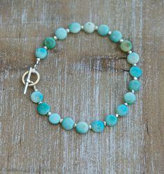 Rustic, earthy Turquoise in light sky blue to deep sea green were joined with sterling silver nuggets to create this bright and cheery bracelet perfect to brighten your day. This is Sleeping Beauty Turquoise from the mine in Arizona. Sterling silver toggle closure. Turquoise gemstones are approximately 7mm and coined shaped and sterling silver faceted nuggets measure 3mm each. Turquoise is a birthstone for December. *If this is a gift and you do not know the exact size, 8 is most common for…