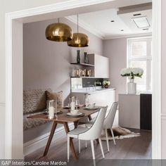 Diese goldfarbenen Deckenleuchten sorgen für den romantischen Look im Essbereich. Die dezente altrosa Farbgebung des Raumes wirkt feminin und zart. Weiße Blumendekoration …