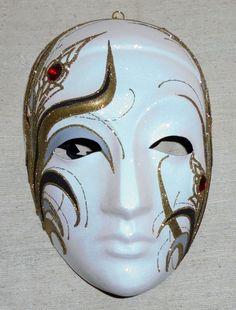 """Een prachtig handgemaakt Venetiaans masker van papier maché en versierd met o.m. Swarovski. Onder de kin is het masker gesigneerd en gedateerd """"Cristina 87"""". Bij de versiering die op het masker is aangebracht is gebruik gemaakt van Swarowski kristal.  Een sticker aan de binnenzijde en een certificaat van echtheid geven aan dat het is gemaakt bij de gerenommeerde maskermakerij La Fucina dei Miracoli in Verona naar een ontwerp van de beeldhouwer Giorgio Arvati.  Het masker is puntgaaf  en…"""