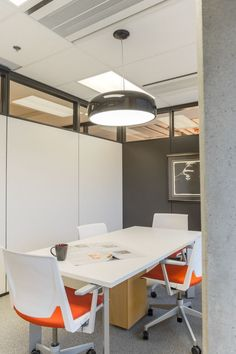 A Flos Smithfield pendant illuminates this corporate boardroom and creates a collaborative atmosphere. Design Commercial design by Elena Del Bucchia Design. Photo by Lori Andrews Photography