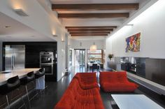 Modern living in a rectangular space with black wood flooring and bright red sofas homefurnituresandiego.com #modern #living