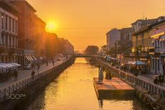 Rain of Sun - Sunset promenade at Naviglio Grande (Grand Canal), an artificial waterway in Milan - Italy. On the banks of the Naviglio formerly lived workers and artisans. Today the Naviglio Grande is a romantic area to stroll. Artists' studios, original shops, romantic pubs, flea markets, and concerts make the area of the Naviglio a unique venue.