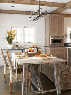 Rustic Simplicity:: Branches and shells aren't the only way to get a natural look  -- instead, try elements that evoke the essence of the aesthetic. Here, rustic character does the trick. Hewn wooden ceiling beams are accented by a weathered-wood farm table and aged cabinets. Textures such as wicker and sun-bleached finishes will help continue the plucked-from-the-outdoors vibe.