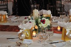 Gala Centerpiece- Winter/Christmas - Hurricane candle holder with fresh hydrangea and burgundy ornaments, over a gold table runner.