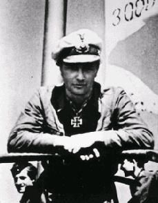 """Korvettenkapitan Johannes Mohr, commander of the """"Edelweiss Boat"""" U-124, returns from patrol in the Atlantic.  Victory pennants can be seen in the background, with each pennant representing a ship sunk and its tonnage."""
