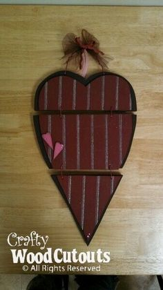 "This February Hanging Heart Wood Craft costs $15.99 and is about 11"" wide and 18.5"" tall."
