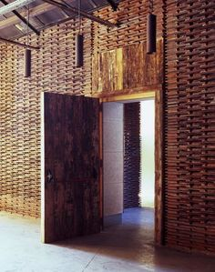 Stacks of reclaimed roof tiles form walls inside this former slaughterhouse in Madrid