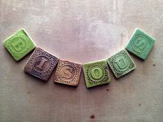 """Tiny Ceramic Letter Magnets Made from Vintage Blocks. These 1"""" x 1"""" tiles are made from imprinting letters from baby blocks on clay. I imagine a custom order used to create a very interesting tile border."""