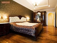 An all-soft, velvet grey on the wall is duly decked up with a carved niche right behind the bed, which is done carefully with cherry-red to Brown Laminated Wood. The inbuilt lights, cast a warm glow on the texture, grains and knots of the bed-backsplash. Brown Bedroom Decor, Wood Ceilings, Modern City, Wood Laminate, Home Look, Townhouse, Lights, Stock Photos, Cherry Red