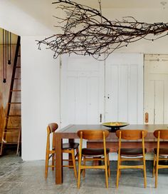 A unique branch chandelier accents the dining area and pairs well with the mid-century style furniture.