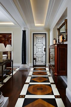 I love this entrance. I love the amazing detailed flooring, the colors that were chosen, the gorgeous glass & iron door, the cove lighting in the ceiling, the black columns, the console table. This is one spectacular & sophisticated space. One of my very favorites....V