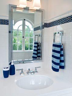 Fantastic white and blue bathroom design featuring white subway tile backsplash with blue mosaic hex inset tiles against crisp white walls.