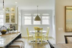 Yellow and gray dining room features a round pedestal dining table lined with yellow windsor dining chairs, Target Threshold Windsor Dining Chairs, illuminated by a Currey and Co Fenchurch Pendant.