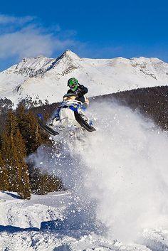 An adventurous snowmobiler takes flight with the San Juan Mountains providing a dramatic backdrop. Near Silverton, Colorado in the Molas Pass area.