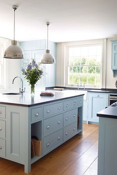 ****modern English country kitchen w/ painted cabinets, wood floor, darker counters ... high neck faucet, metal pendants add industrial/farmhouse touches, designer Penny Morrison .