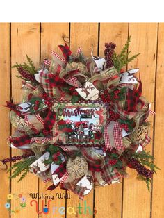 """THis charming Country Christmas Wreath is perfect for those who love the country farmhouse theme! This Country Christmas wreath includes a fun sign picturing a tractor and fabric Christmas trees the sign reads"""" Christmas In The Country"""" written out in wooden letters. The fun ribbons included are plaids, browns, and even a fun deer pattern! This Country wreath is also full of fun ornaments including wooden snowflakes, pine picks, and berries!"""