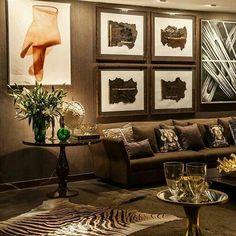 Living com papel de parede e sofá chocolate/marrom, mesa lateral café, tapete de onça e ornamentos.