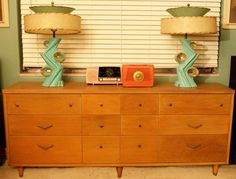 Mid century dresser accessorized  with matching turquoise lamps and  pink and coral radios.